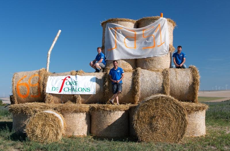 Nicolas Kunysz, Adrien Foy et Florent Lagille posent devant la structure de paille achevée le 10 août par les JA du canton de Vitry. (Crédit: G. Perrin)